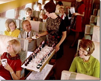 Flight attendant serving alcohol from serving cart.